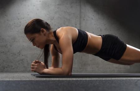 Photo pour woman doing plank exercise on mat in gym - image libre de droit