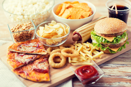 Photo pour close up of fast food snacks and cola drink on wooden table - image libre de droit
