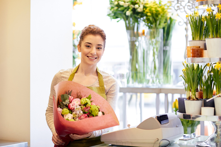 Photo for people, business, sale and floristry concept - happy smiling florist woman holding bunch of flowers wrapped into paper at flower shop - Royalty Free Image