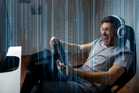 Photo pour technology, gaming, entertainment and people concept - young man in headphones with pc computer playing car racing video game at home and steering wheel - image libre de droit