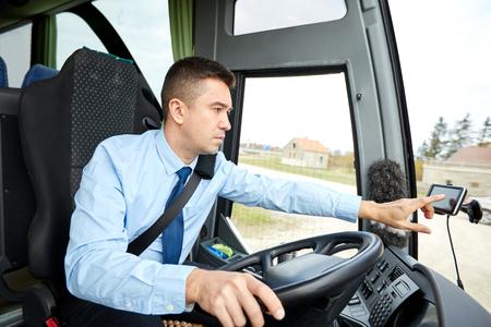transport, transportation, navigation and people concept - bus driver entering address to gps navigator