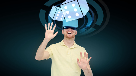Photo pour 3d technology, virtual reality, cyberspace, entertainment and people concept - happy young man with virtual reality headset or 3d glasses playing game with casino dice projection over black background - image libre de droit