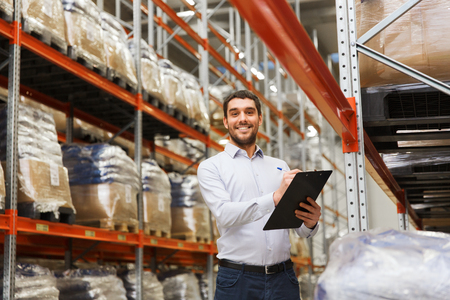 Photo pour wholesale, logistic, business, export and people concept - man or manager with clipboard checking goods at warehouse - image libre de droit