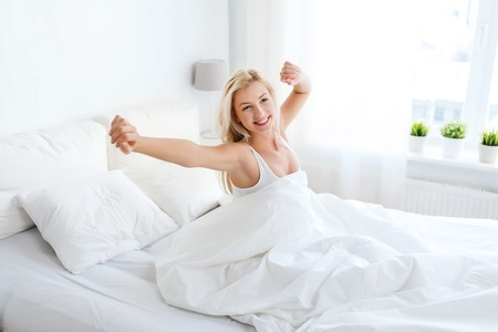 Foto de rest, sleeping, comfort and people concept - young woman stretching in bed at home bedroom - Imagen libre de derechos