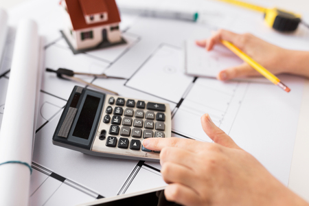 business, architecture, building, construction and people concept - close up of architect hand with blueprint counting on calculator