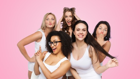friendship, beauty, body positive and people concept - group of happy plus size women in white underwear having fun and making faces over pink background