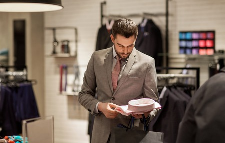 Foto per sale, shopping, fashion, style and people concept - elegant young man in suit choosing shirt in mall or clothing store - Immagine Royalty Free