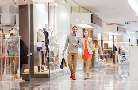 Foto de sale, consumerism and people concept - happy young couple with shopping bags walking in mall - Imagen libre de derechos
