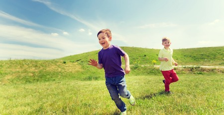 Foto de summer, childhood, leisure and people concept - happy little boys playing tag game and running outdoors on green field - Imagen libre de derechos