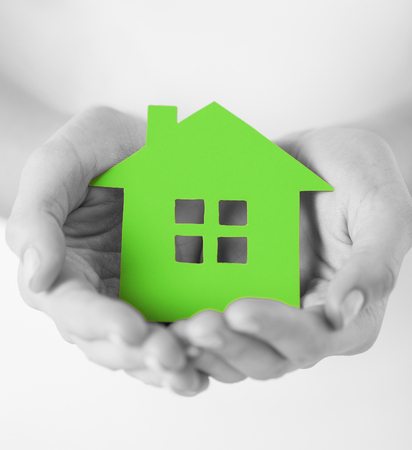 Photo pour real estate and family home concept - closeup picture of female hands holding green blank paper house - image libre de droit