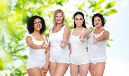 Photo pour gesture, friendship, beauty, body positive and people concept - group of happy different women in white underwear showing thumbs up over green natural background - image libre de droit