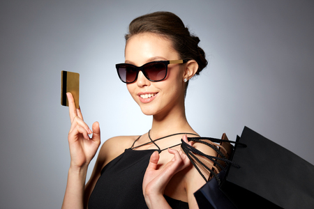 Photo pour sale, finances, fashion, people and luxury concept - happy beautiful young woman in black sunglasses with credit card and shopping bags over gray background - image libre de droit