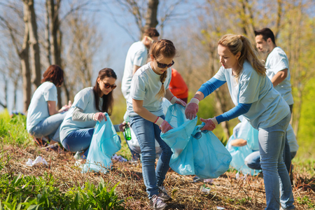 Foto per volunteering, charity, cleaning, people and ecology concept - group of happy volunteers with garbage bags cleaning area in park - Immagine Royalty Free