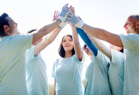 Photo pour volunteering, charity, people, gesture and ecology concept - group of happy volunteers making high five in park - image libre de droit