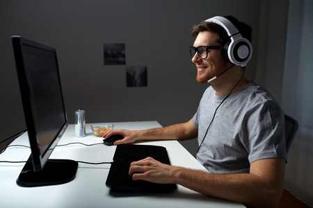 technology, gaming, entertainment, let\'s play and people concept - happy young man in headset and glasses with pc computer playing game at home and streaming playthrough or walkthrough video