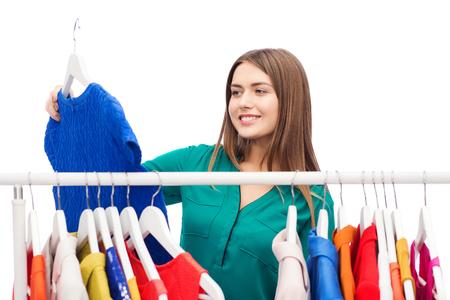 Foto de clothing, shopping, fashion, style and people concept - happy woman choosing clothes at home wardrobe - Imagen libre de derechos