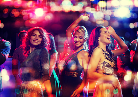 Foto de party, holidays, celebration, nightlife and people concept - happy friends dancing in club with holidays lights - Imagen libre de derechos