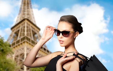sale, fashion, tour, people and luxury concept - happy beautiful young woman in black sunglasses with shopping bags over paris eiffel tower backgroundの写真素材
