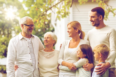 Photo pour family, happiness, generation, home and people concept - happy family standing in front of house outdoors - image libre de droit