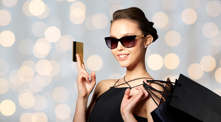 Foto de sale, finances, fashion, people and luxury concept - happy beautiful young woman in black sunglasses with credit card and shopping bags over holidays lights background - Imagen libre de derechos