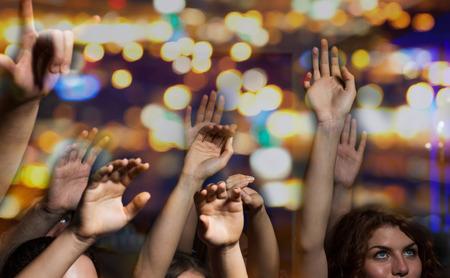 Foto de party, holidays, music, nightlife and people concept - close up of happy people at concert in night club waving hands - Imagen libre de derechos