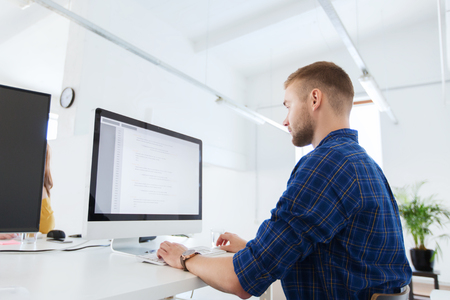 business, technology, education and people concept - young creative man or programmer with computer working at office