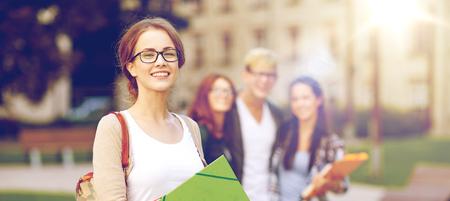 Foto de education, campus, friendship and people concept - group of happy teenage students with school folders - Imagen libre de derechos