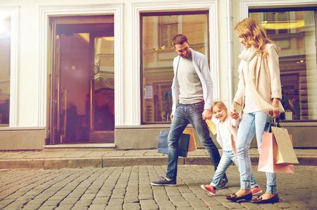 Foto de sale, consumerism and people concept - happy family with little child and shopping bags in city - Imagen libre de derechos
