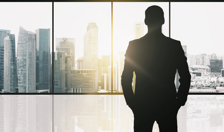 Photo pour business and people concept - silhouette of businessman over office window and singapore city skyscrapers background and sun light - image libre de droit