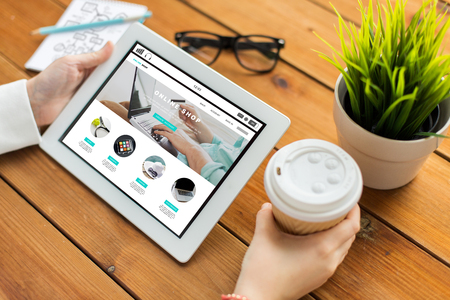 Photo for business, internet shopping, technology and people concept - close up of woman with online shop web page on tablet pc computer screen, notebook and coffee on wooden table - Royalty Free Image