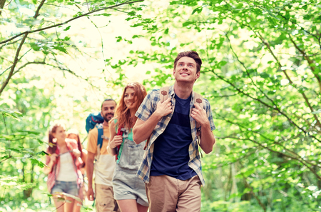 Photo for adventure, travel, tourism, hike and people concept - group of smiling friends walking with backpacks in woods - Royalty Free Image