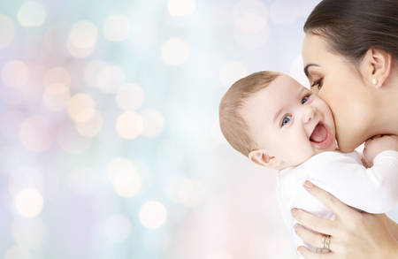 Photo pour family, motherhood, parenting, people and child care concept - happy mother kissing adorable baby over blue holidays lights background - image libre de droit