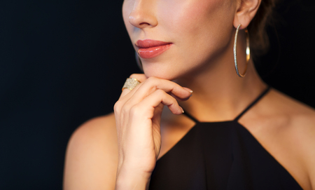 Foto de people, luxury, jewelry and fashion concept - beautiful woman in black wearing diamond earring and ring over dark background - Imagen libre de derechos