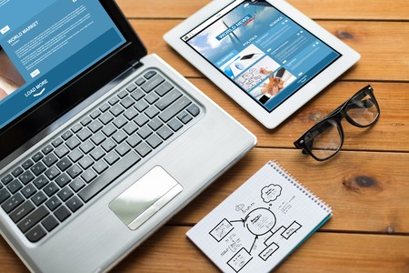 Photo pour business, responsive design and technology concept - close up of on laptop computer, tablet pc, notebook and eyeglasses with world news and scheme on wooden table - image libre de droit