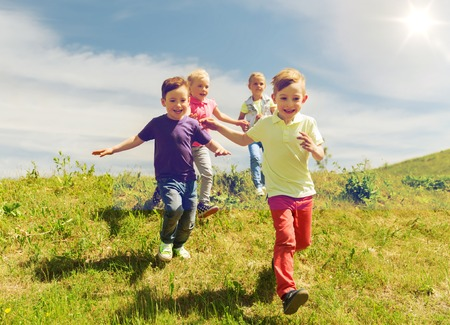 Photo for summer, childhood, leisure and people concept - group of happy kids playing tag game and running on green field outdoors - Royalty Free Image