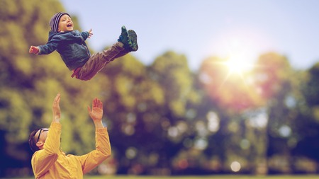 Foto de family, childhood, fatherhood, leisure and people concept - happy father and little son playing and having fun outdoors over summer park background - Imagen libre de derechos
