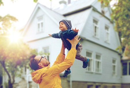 Foto de family, childhood, fatherhood, leisure and people concept - happy father and little son playing and having fun outdoors over living house background - Imagen libre de derechos