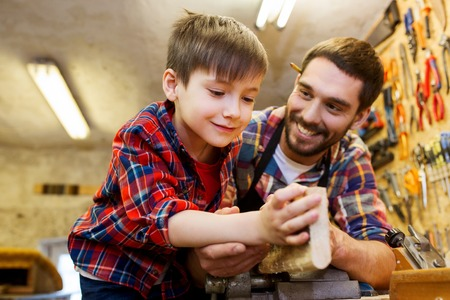 Photo pour family, carpentry, woodwork and people concept - father and little son working with wood plank at workshop - image libre de droit