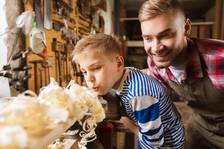 Photo pour family, carpentry, woodwork and people concept - father and little son blowing shavings off wood plank at workshop - image libre de droit