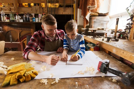 Photo for family, carpentry, woodwork and people concept - happy father and little son with blueprint at workshop - Royalty Free Image