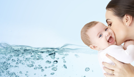 Photo pour family, motherhood, people and child care concept - happy mother kissing adorable baby over blue background with water splash - image libre de droit