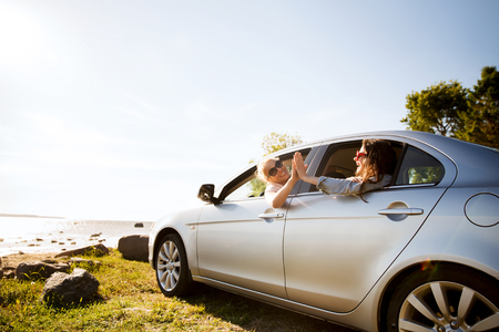 Photo for summer vacation, holidays, travel, road trip and people concept - happy teenage girls or young women in car at seaside making high five gesture - Royalty Free Image