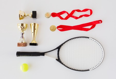 Photo pour sport, achievement, championship, competition and success concept - close up of tennis racket and ball with cups and medals over white background - image libre de droit