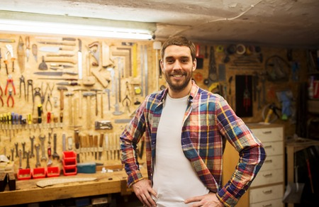 Photo for profession, people, carpentry and people concept - happy man or carpenter in checkered shirt standing at workshop wall with work tools - Royalty Free Image
