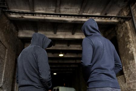 Photo pour criminal activity, addiction, people and social problem concept - close up of addict men or criminals in hoodies on street - image libre de droit