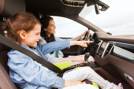 Photo pour family, transport, road trip and people concept - happy woman with little daughter driving in car - image libre de droit