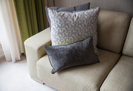 comfort, furniture and interior concept - close up of couch with cushions at home living room