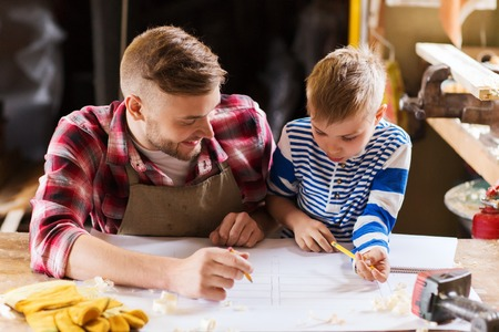 Photo pour family, carpentry, woodwork and people concept - happy father and little son with blueprint at workshop - image libre de droit