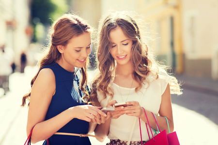 Foto de sale, consumerism and people concept - happy young women with shopping bags and smartphone on city street - Imagen libre de derechos
