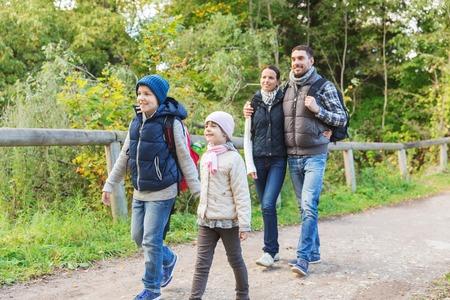 Foto de adventure, travel, tourism, hike and people concept - happy family walking with backpacks in woods - Imagen libre de derechos
